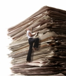 Business Woman Climbing a Pile of Files